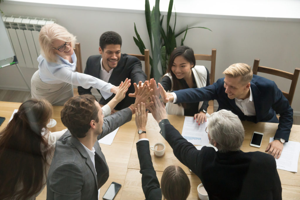 Diverse motivated multi-ethnic business team giving high five showing unity concept, young and old corporate group join hands promising support in collaboration, help commitment in teamwork, top view