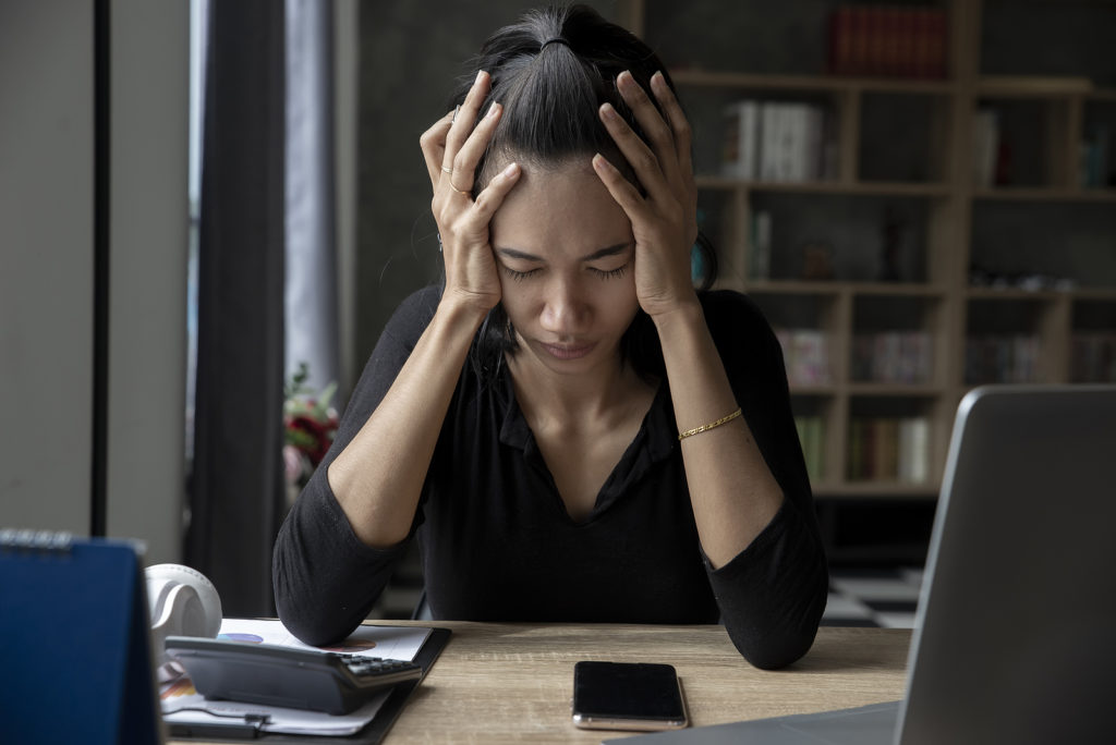 Stressed businesswoman, Frustrated and upset in business pressure and overworked at home office. Adult Asian female working on laptop, feeling tire and headache. Stressed and Frustrated concept.
